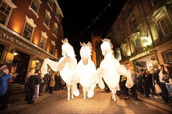 Three illuminated horses in street at night